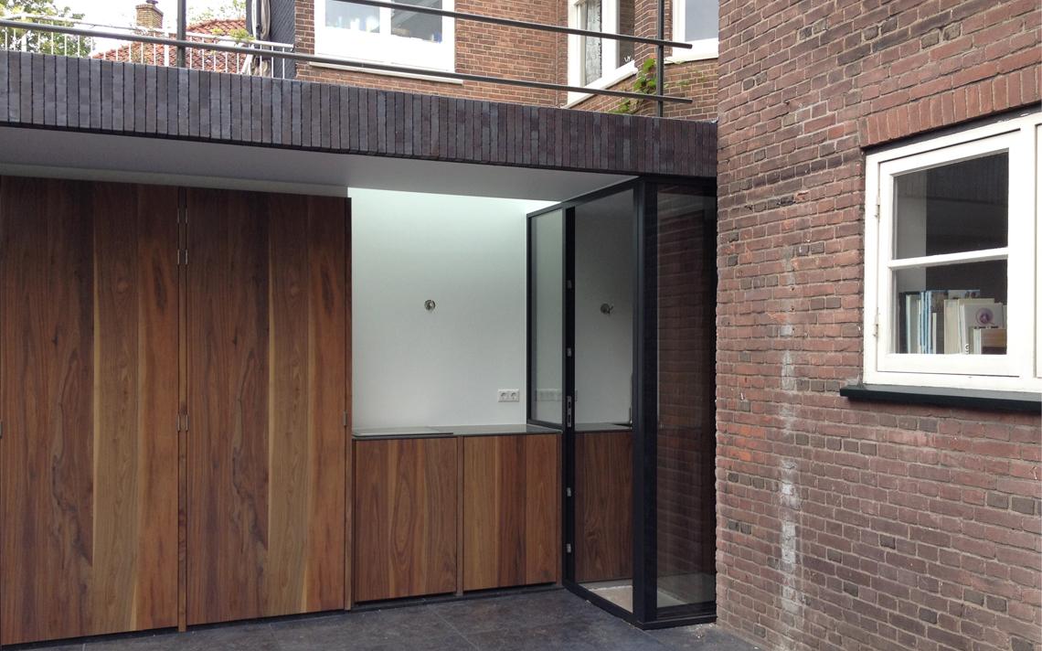 aanbouw baksteen en hout rollaag deur van glas en staal